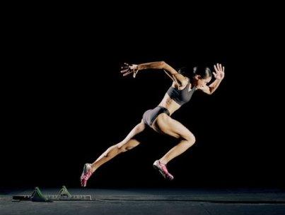 Female athlete running from starting blocks, black background